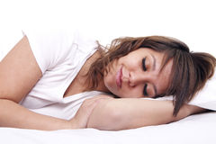 Sleep and dreams. A young woman sleeps in bed, set against a white background Stock Image