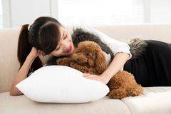 Sleep, honey!. Portrait of a girl lying on a cushion with a puppy stock photo