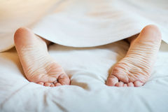 Sleep. Laziness and sleep, feet in the bed Royalty Free Stock Images