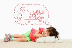 Sleep ride. Portrait of small girl lying and dreaming about riding a horse Royalty Free Stock Photos