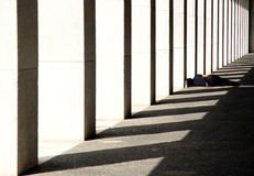 Sleep in the shadows. A woman, lying asleep on the ground under an geometric arcade and arches form of artistic shadows Royalty Free Stock Images