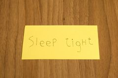 Sleep tight handwrite on a yellow paper with a pen on a table. Composition stock images