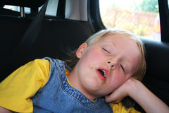 Sleep time. Child who has fallen asleep in the car after a feed her face has food stains Stock Photos