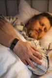 Sleep Tracking. Wristband and a sleeping man Stock Photo