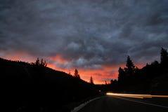 _sleep van auto licht aan:steken omhoog de silhouet van een vallen van de avond berg scène als de zon reeks achter het stock afbeeldingen