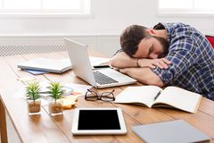 Sleeping overworking businessman with laptop in modern white office Royalty Free Stock Photos