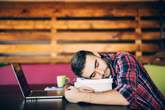 Sleep at work. Young man over tired at work and asleep on books royalty free stock images