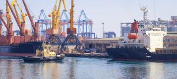 Sleepboot bij de boog die van vrachtschip, het schip bijstaan om in Haven te manoeuvreren royalty-vrije stock fotografie