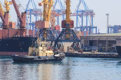Sleepboot bij de boog die van vrachtschip, het schip bijstaan om in Zeehaven te manoeuvreren stock afbeeldingen