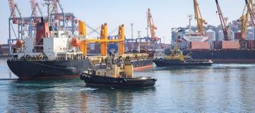 Sleepboot bijwonend die Vrachtschip in de Haven van Odessa, de Oekraïne wordt gemanoeuvreerd stock foto's
