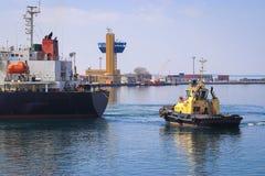 Sleepboot bijwonend die Vrachtschip in de Haven van Odessa, de Oekraïne wordt gemanoeuvreerd stock afbeeldingen