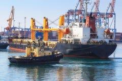 Sleepboot bijwonend die Vrachtschip in de Haven van Odessa, de Oekraïne wordt gemanoeuvreerd stock fotografie