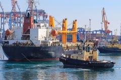Sleepboot bijwonend die Vrachtschip in de Haven van Odessa, de Oekraïne wordt gemanoeuvreerd royalty-vrije stock afbeelding