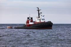 Sleepboot die in wachttijd op kalme oceaan bij anker drijven Stock Foto's