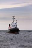 Sleepboot die in wachttijd op kalme oceaan bij anker drijven Stock Afbeeldingen