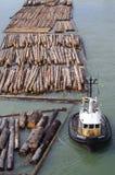 Sleepboot en timmerhout stock afbeelding