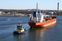Sleepboot met vrachtschip stock foto's