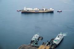 Sleepboten die containerschip bijstaan stock afbeeldingen
