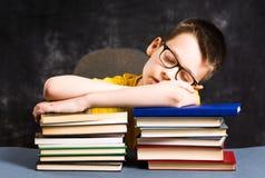 sleepeing在书顶部的男孩 库存照片