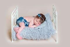 Sleepin recién nacido de la muchacha en el pesebre Foto de archivo libre de regalías
