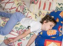 Sleepinchild relaja al hijo de reclinación del resto del muchacho Fotografía de archivo libre de regalías