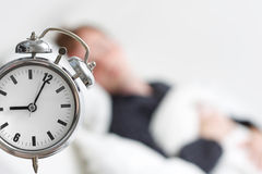 Sleeping. A man sleeping with an alarm clock in the foreground Royalty Free Stock Image