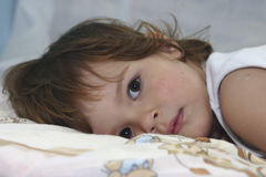 Almost sleeping. Little child lying in bed Royalty Free Stock Photos