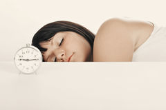 Sleeping. Long woman with alarm clock. Focused on face. Auburn tint Royalty Free Stock Photos