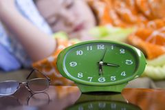 Sleeping. Green clock and glasses with a female sleeping in the background(shallow dof stock photo