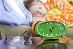 Sleeping in. Alarm clock with young female sleeping (focus on clock stock photography
