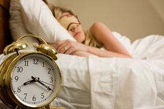 Sleeping in. Blond woman sleeping in bed with eye cover on with focus on the alarm clock time being after eight o'clock Royalty Free Stock Images