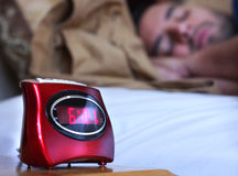 Sleeping In. A man sleeping in bed with a focused alarm clock in the foreground Royalty Free Stock Photos