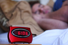 Sleeping In. A man sleeping in bed with a focused alarm clock in the foreground Royalty Free Stock Photography