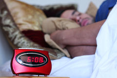 Sleeping In. A man sleeping in bed with a focused alarm clock in the foreground Royalty Free Stock Image