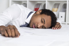 Sleeping African American clerk in office. Close up of a tired African American clerk who has laid his head on a table and is sleeping. Concept of overworking Royalty Free Stock Photos