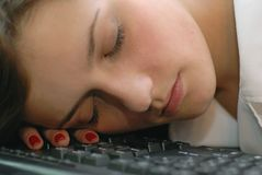 Sleeping again. Beautiful women sleeping on keyboard Royalty Free Stock Photography