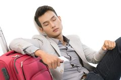 Sleeping in airport. Portrait of young businessman sleeping in airport with his luggage near by royalty free stock photography