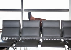 Sleeping in the airport man. Put his foot on the seat back royalty free stock image