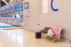 Sleeping at airport. SHANGHAI, CHINA - DEC 29, 2106: Man sleeping at airport, holding his suitcase. Shanghai Pudong International Airport is international royalty free stock photo