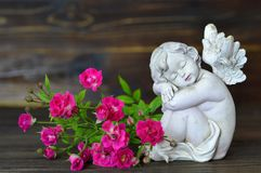Sleeping angel and roses on wooden background Royalty Free Stock Image
