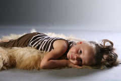 Sleeping on animal rug. A young girl lies belly-down on an animal-skin rug Stock Image