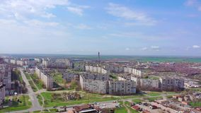 Sleeping area of the city. You can see houses, streets, a large chimney. On the horizon are spring fields. Aerial shooting stock footage