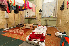 Sleeping area for refugee and refugees` clothes is drying of on the rope in the temporary apartment. Royalty Free Stock Photos