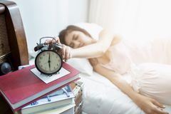 Sleeping asia woman and alarm clock is waking up. At 6.00 AM Royalty Free Stock Photo