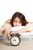 Sleeping Asian girl with alarm clock Royalty Free Stock Photos