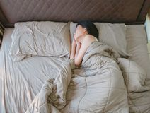 Sleeping Asian woman lying on bed, top view.  Royalty Free Stock Images