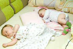 Sleeping babies. Two cute babies sleeping in one bed royalty free stock photo