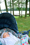 Sleeping baby. In the carriage by the lake,fresh air and natural environment Royalty Free Stock Photography