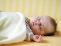 Sleeping baby. In yellow bed Stock Image