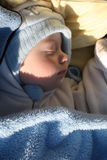 Sleeping baby. With cap on and sunlight on his face Royalty Free Stock Photos